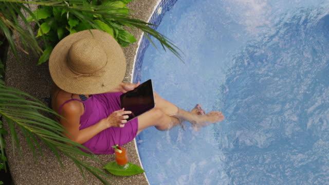 Woman sitting on edge of hot tub using digital tablet. video