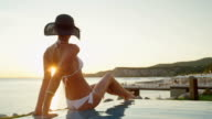 CLOSE UP: Woman sitting on edge of infinity pool and watching vibrant ocean bay video
