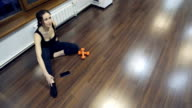 woman sitting on floor, gets up, goes to the fitness studio video