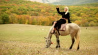 Woman sitting on horse while it is grazing video