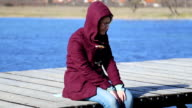woman sitting on lake dock alone video