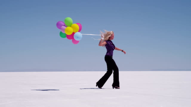 Woman skipping with balloons at salt flat video