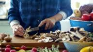 Woman slicing mushroom on wooden board in kitchen video