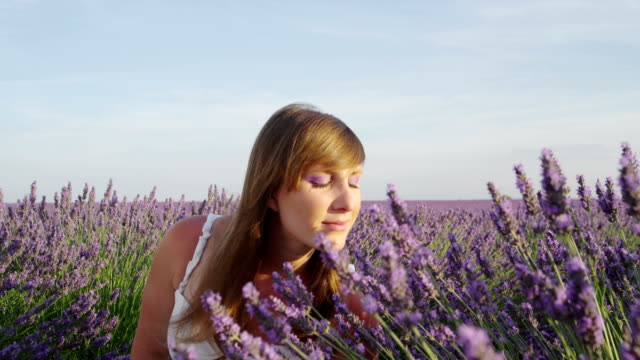 SLOW MOTION CLOSE UP: Woman smelling scented flowers in beautiful lavender field video