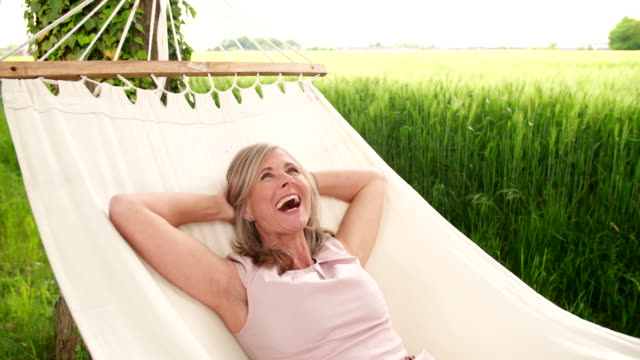 Woman smiling at the camera while relaxing in a hammock video