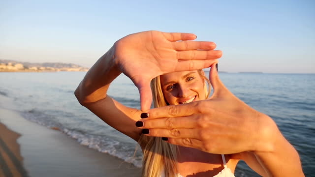 Woman smiling through frame made from fingers video