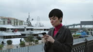 Woman sms texting using app on smartphone in port video