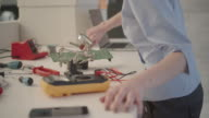 Woman Soldering a circuit board in her office. video