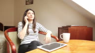 Woman speaking at the mobile phone while using her digital tablet. video