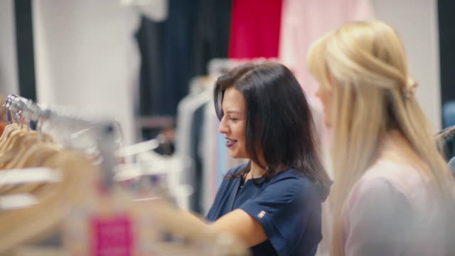 Woman spending time in the shop. Two girlfriends try on clothes video
