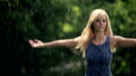 Woman spinning in summer rain video