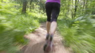 TS Woman sprinting across a path through forest video