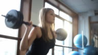 A woman squats with a barbell behind head in front of large windows video