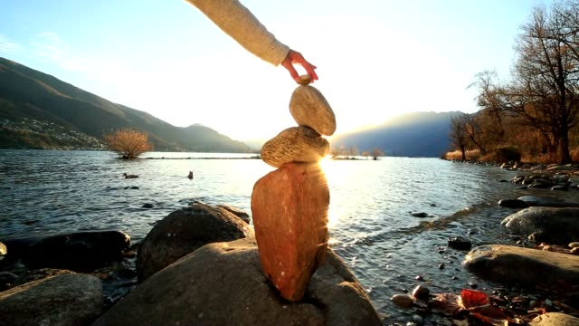 Woman stacking rocks by the lake video