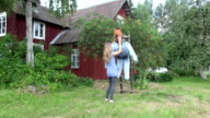 woman stand scarecrow on cherry tree to protect berries from birds. FullHD video