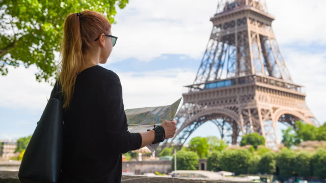 Woman standing across from Eiffel Tower, exploring Paris with map video