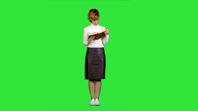 Woman standing and reading book on a Green Screen, Chroma Key video