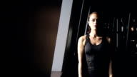 Woman standing at the window smiling and engaged with dumbbells video