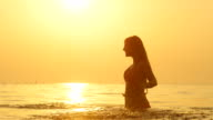 SLOW MOTION: Woman standing in ocean, raising hands up and splashing water video
