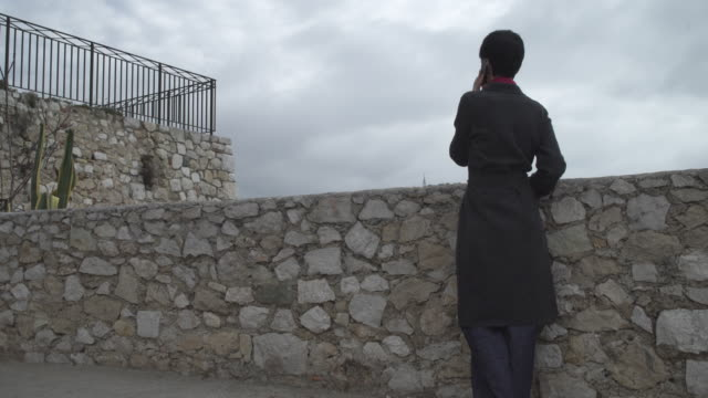 Woman standing near the stonewall using smartphone video
