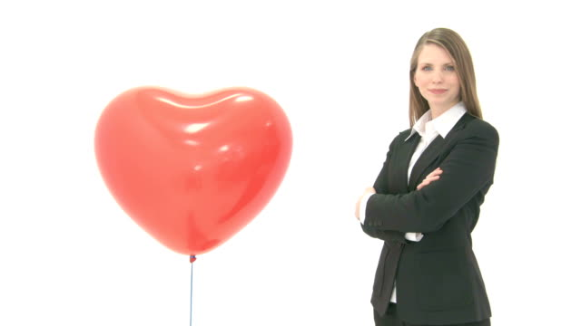 Woman standing next to lifting heart balloon video