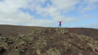 AERIAL: Woman standing on crater of volcano with hands raised video