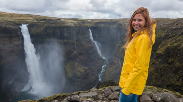 Woman standing on edge of canyon, looking down at waterfalls video