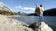 Woman standing on rock above lake, arms outstretched video