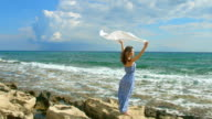 Woman standing on seashore, white scarf waving in the wind video