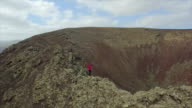 AERIAL: Woman standing on the edge of volcano crater video