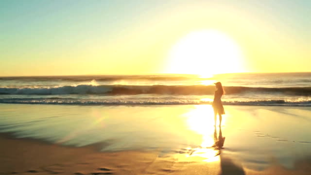 Woman stands alone on a beach video