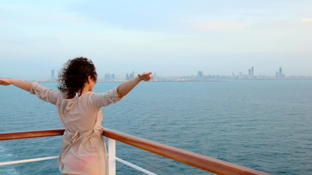 Woman stands on deck of ship sailing out city video