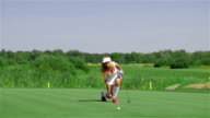 Woman stands on her knee at the golf video