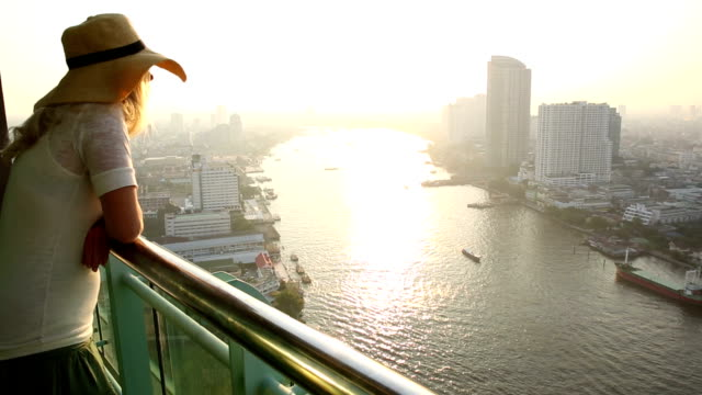 Woman stands on hi-rise deck, looks out across city, river video
