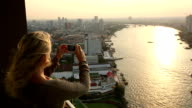 Woman stands on hi-rise deck, takes pic of city, river video