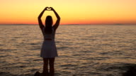 AERIAL, CLOSE UP: Woman staring at rippling sea and making heart shaped sign video