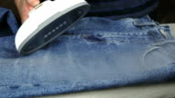 Woman steaming denim fabric on ironing table video