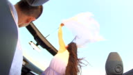 HD SUPER SLOW-MOTION: Woman Sticking Sheet Out Of Convertible video