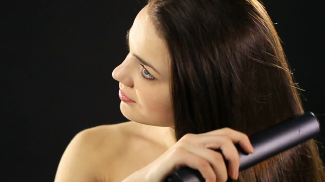 Woman straightening her hair video