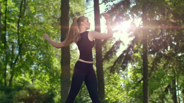 Woman stretching in park at evening. Young female runner warm up outdoor video