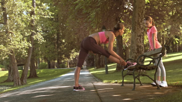 DS Woman stretching on a park bench and talking to her daughter video
