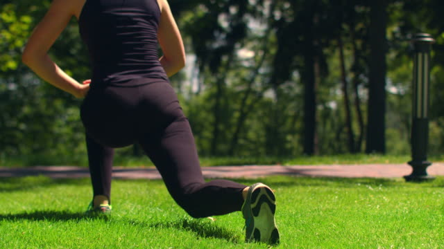 Woman stretching outdoor. Fitness girl doing lunges in park. Workout and fitness video