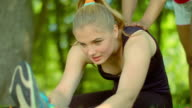 Woman stretching outdoor. Sporty girl help to do stretching exercises video