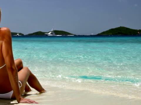 woman sunbathing by a beach shoreline in the Virgin Islands video