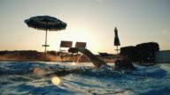 Woman swimming at sunset in idyllic resort video