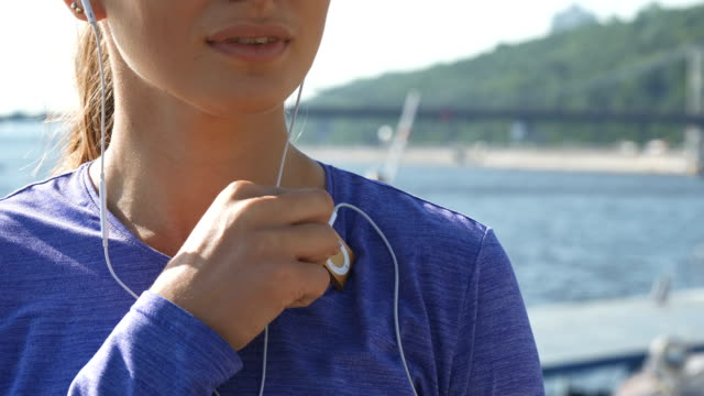Woman switches on her mp3 player and enjoys music video