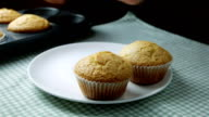 Woman take fresh baked muffins out of muffins tin and place them on the plate video