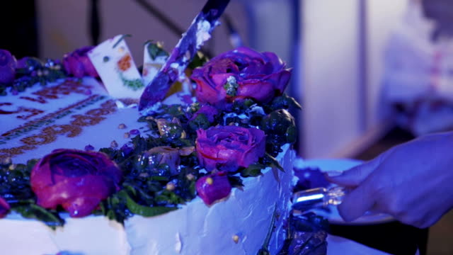 Woman take piece of huge cake with roses by knife at celebration event video