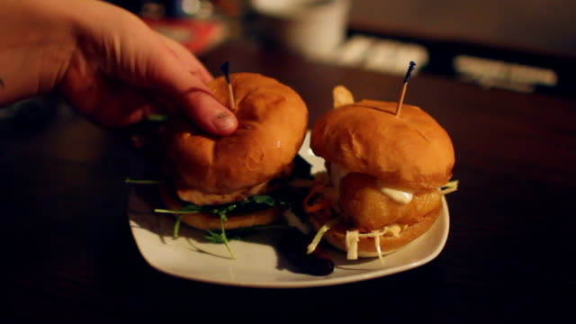 Woman takes burger from plate video