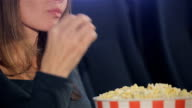 Woman takes flakes of popcorn from the bucket video